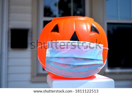 Coronavirus Halloween Pumpkin. Halloween jack o lantern wearing a covid-19 face mask and placed outside a home at daytime. House, front door, and window visible in background.