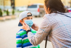 Coronavirus, illness, infection, quarantine, medical mask, COVID-19. Mother puts her son a face protective mask outdoors. Stop coronavirus spreading. Coronavirus quarantine. Coronavirus outbreak.