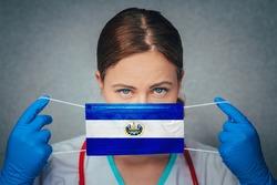 Coronavirus in El Salvador Female Doctor Portrait hold protect Face surgical medical mask with El Salvador National Flag. Illness, Virus Covid-19 in El Salvador, concept photo