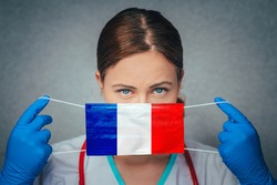 Coronavirus in France. Female Doctor Portrait hold protect Face surgical medical mask with France National Flag. Illness, Virus Covid-19 in France, concept photo