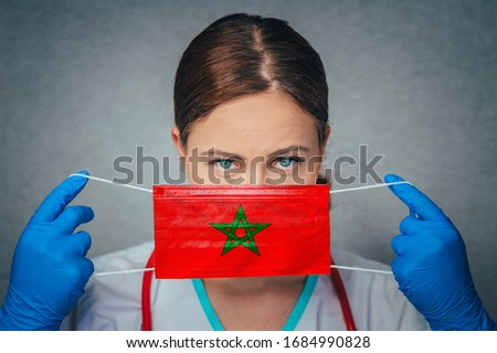 Coronavirus in Morocco Female Doctor Portrait hold protect Face surgical medical mask with Morocco National Flag. Illness, Virus Covid-19 in Morocco, concept photo