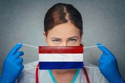 Coronavirus in Netherlands Female Doctor Portrait hold protect Face surgical medical mask with Netherlands National Flag. Illness, Virus Covid-19 in Netherlands, concept photo