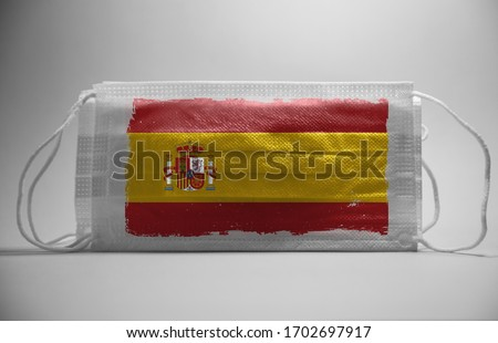 Coronavirus in Spain Concept.Dramatic atmosphere Spain Flag printed on surgical protective mask.Impact of pandemic virus to spain economy.Covid -19 spread around spain and rest of europe.covid-19
