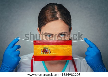 Coronavirus in Spain, Female Doctor Portrait hold protect Face surgical medical mask with Spain National Flag. Illness, Virus Covid-19 n Spain, concept photo