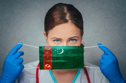 Coronavirus in Turkmenistan Female Doctor Portrait hold protect Face surgical medical mask with Turkmenistan National Flag. Illness, Virus Covid-19 in Turkmenistan, concept photo