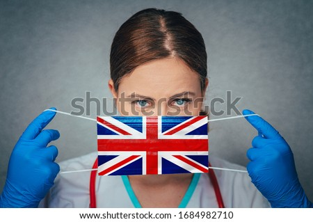 Coronavirus in United Kingdom, Great Britain, England Female Doctor Portrait hold protect Face surgical medical mask with United Kingdom National Flag. Illness, Virus Covid-19 in United Kingdom,