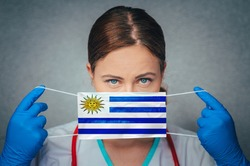 Coronavirus in Uruguay Female Doctor Portrait hold protect Face surgical medical mask with Uruguay National Flag. Illness, Virus Covid-19 in Uruguay, concept photo