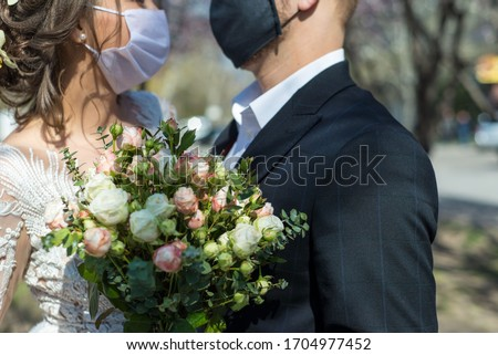 coronavirus infection Portrait of a masked bride and groom during a wedding ceremony. Oudoor. Weddings during the period of quarantine and pandemic of coronavirus infection
