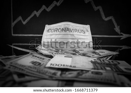 Coronavirus inscription on a medical mask on top of world international banknotes, in the background a blackboard with a stock chart with a negative trend. US dollars and Euro Coronavirus warning.