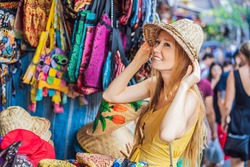 Coronavirus is over. Quarantine weakened. Take off the mask. Now you can travel. Woman traveler choose souvenirs in the market at Ubud in Bali, Indonesia