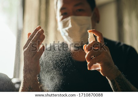 Coronavirus. Man wearing in medical protective mask cleaning hands with sanitizer spray in house to prevent Coronavirus, Covid-19, flu. Spray bottle. Virus and illness protection. Stock foto ©