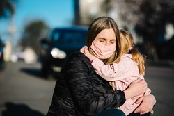 Coronavirus. Mom hugs the baby and says goodbye. Woman in a protective mask embrace daughter on the street. Preventive measures against Covid-19 infection. Illness protection. Quarantine.