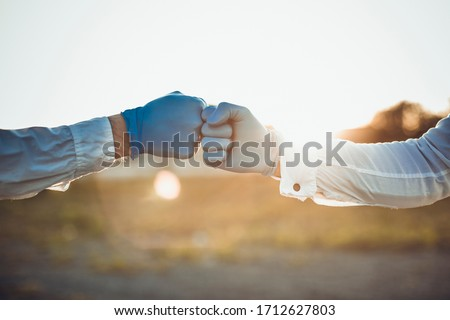 Coronavirus or covid-19 bacteria spread by handshake or touch concept. Say No to Handshake. Businessman handshake and virus spread. Doctors holding hands together as colleagues wearing black gloves.