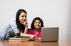 Coronavirus Outbreak and education concept - Lockdown and school closures. Indian Mother helping daughter studying online classes at home. COVID-19 pandemic forces children and teachers e-learning