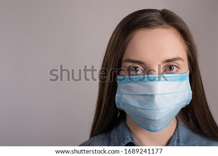 Coronavirus outbreak concept. Close up photo of woman wearing facial medical mask protecting against pandemic isolated over grey background with copy empty space