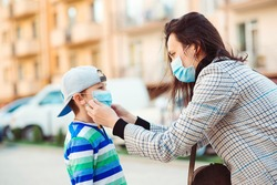 Coronavirus outbreak. Mother puts her son a face protective mask outdoors. Stop the coronavirus spreading. Quarantine. Protective measures. Public crowded place. People prevent infection from virus.