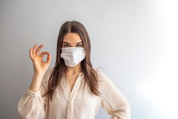 Coronavirus outbreak: Woman with a medical disposable mask to avoid contagious viruses, Showing OK sign. Corona virus prevention. Concept of coronavirus quarantine. Attention