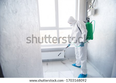Coronavirus Pandemic. A disinfector in a protective suit and mask sprays disinfectants in house or office. Protection agsinst COVID-19 disease. Prevention of spreding pneumonia virus with surfaces. Stockfoto ©