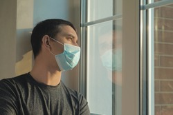 Coronavirus pandemic covid-19 and quarantine concept. Man in a medical mask near window. Man tired of quarantine of Coronavirus. Sick sad man in medical protective face mask looking through window.