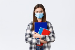 Coronavirus pandemic, covid-19 education, and back to school concept. Young female student in medical mask holding notebooks, going to class, freshman in university in personal protective facemask
