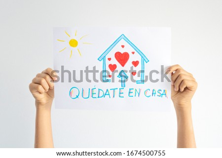 Coronavirus pandemic self quarantine in Spain. Kid hands holding drawing picture with spanish words Quedate en casa - Stay at home