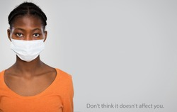 Coronavirus Pandemic. Serious african woman in medical mask on a gray background with space for text and slogan