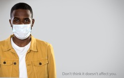 Coronavirus Pandemic. Serious africanamerican man in medical mask on a gray background with space for text and slogan