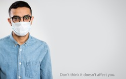 Coronavirus Pandemic. Serious arab young man in medical mask on a gray background with space for text and slogan