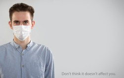Coronavirus Pandemic. Serious caucasian young man in medical mask on a gray background with space for text and slogan