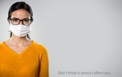 Coronavirus Pandemic. Serious hispanic young woman in medical mask on a gray background with space for text and slogan