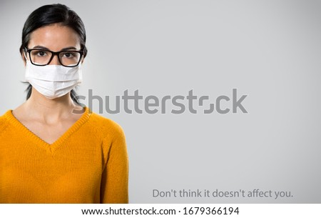 "Coronavirus Pandemic. Serious hispanic young woman in medical mask on a gray background with space for text and slogan ""Don't think it doesn't affect you""."