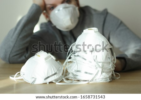 Coronavirus panic concept. Virus protection respirator masks on the table and a worried woman in blurred background. N95, FFP2, COVID-19.