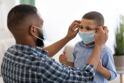 Coronavirus Prevention. Black Dad Putting On Protective Surgical Mask On Son's Face Before Walk Standing At Home. Covid-19 Protection And Healthcare Concept. Selective Focus