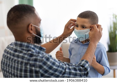 Coronavirus Prevention. Black Dad Putting On Protective Surgical Mask On Son's Face Before Walk Standing At Home. Covid-19 Protection And Healthcare Concept. Selective Focus ストックフォト ©