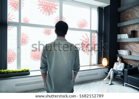 Coronavirus quarantine concept. Young couple looking and scared about covid viruses outside. Stay at home self isolation. Stock photo ©