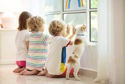 Coronavirus quarantine. Stay home. Kids sitting at window. Children drawing rainbow sign of hope. Boy and girl during corona virus lockdown. Child and pet. Family isolation indoors. Disease prevention