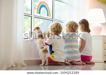 Coronavirus quarantine. Stay home. Kids sitting at window. Children drawing rainbow sign of hope. Boy and girl during corona virus lockdown. Child and pet. Family isolation indoors. Disease prevention