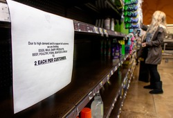 Coronavirus related sign rationing food at a supermarket with shopper in the distance