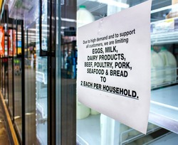Coronavirus related sign rationing food such as dairy products ,meat,seafood,bread and eggs at a supermarket. The shelves of the cooler are fairly empty