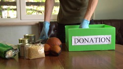 Coronavirus Relief Funds and Donations. Volunteer in the Protective Medical Mask and hand Gloves Putting Food In Donation Box. Charity donations. Making Donations To Food Bank