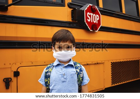 Coronavirus school reopening concept: a school boy stands in front of a school bus wearing a face mask and backpack. Stop sign is visible. Covid-19, health, education, safety, and back to school.