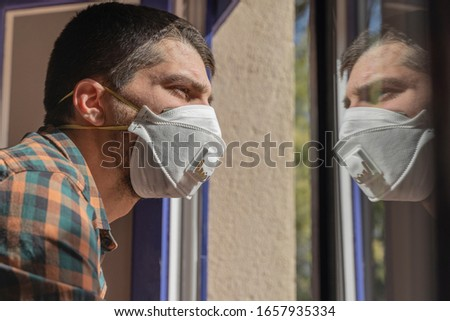 Coronavirus. Sick man of corona virus  looking through the window and wearing mask protection and recovery from the illness in home.