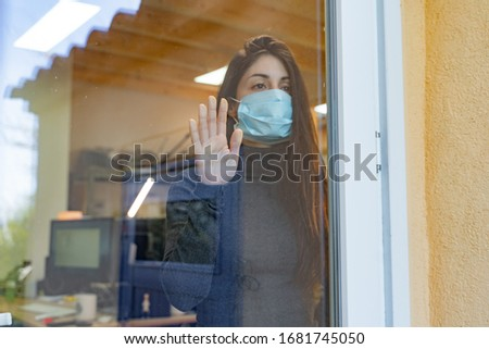 Coronavirus. Sick woman of corona virus  looking through the window and wearing mask protection and recovery from the illness at hospital. Quarantine. Patient at hospital. Prevent infection.