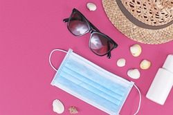 Coronavirus summer 2020 crisis concept with face mask, straw hat, sunglasses, disinfectant spray bottle and seashells on pink background