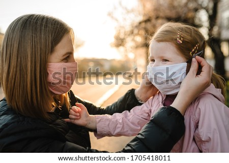 Coronavirus the end concept. No more covid-19. Little girl, mother wear masks walk on street. Mom removes mask happy child. Family with kid outdoors. celebrating success. Pandemic is over, has ended.