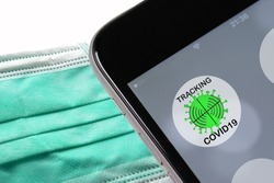 Coronavirus tracking or tracing application to reduce coronavirus spreading after quarantine detecting infected people. close up on Phone with app in caucasian hands
