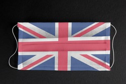 Coronavirus update in Great Britain. UK healthcare concept. Flag of Great Britain printed on medical mask on black background. Covid-19 outbreak.  Spread of corona virus in Europe.