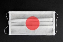 Coronavirus update in Japan. Japanese healthcare concept. Flag of Japan printed on medical mask on black background. Covid-19 outbreak.  Spread of corona virus in Asia.
