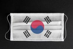 Coronavirus update in South Korea. South Korean healthcare concept. Flag of South Korea printed on medical mask on black background. Covid-19 outbreak.  Spread of corona virus in Asia.