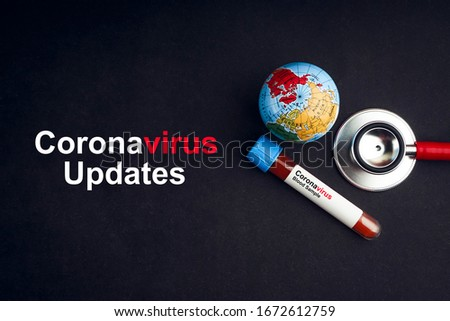 CORONAVIRUS UPDATES text with stethoscope, world globe and blood sample vacuum tube on black background. Covid-19 or Coronavirus Concept